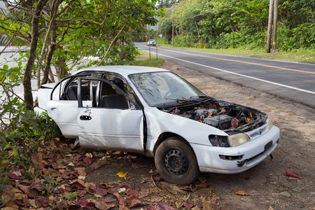 KAHANA BAY, OAHU, HAWAII - FEBRUARY 20, 2017: Abandoned and stripped white sedan car along the highway on the North Shore of Oahu Hawaii.