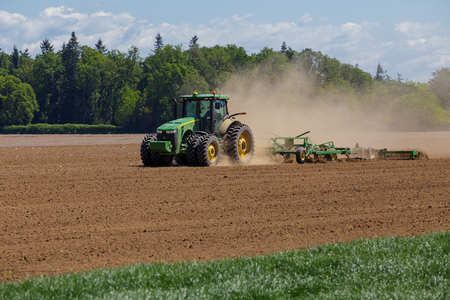 ALBANY, OR - MAY 7, 2015: John Deere commercial tractor plowing a field at a farm near Albany Oregon getting ready to plant seeds for food to grow. Editorial