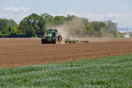 ALBANY, OR - MAY 7, 2015: John Deere commercial tractor plowing a field at a farm near Albany Oregon getting ready to plant seeds for food to grow.