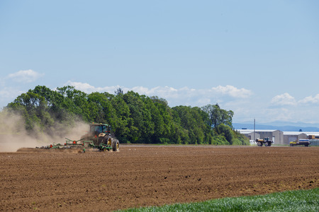 rancheros: ALBANY, OR - MAY 7, 2015: John Deere commercial tractor plowing a field at a farm near Albany Oregon getting ready to plant seeds for food to grow. Editorial