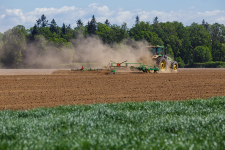 rancheros: ALBANY, O - el 7 de mayo de 2015: John Deere tractor comercial arando un campo en una granja cerca de Albany Oregon preparándose para plantar semillas para que los alimentos crezcan. Editorial