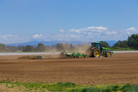 growers: ALBANY, OR - MAY 7, 2015: John Deere commercial tractor plowing a field at a farm near Albany Oregon getting ready to plant seeds for food to grow. Editorial