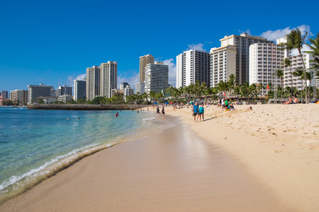 HONOLULU, OAHU, HAWAII - FEBRUARY 22, 2017: Waikiki Beach and the city of Honolulu on Oahu Hawaii with tourists and locals on the beach and in the water of the Pacific Ocean.