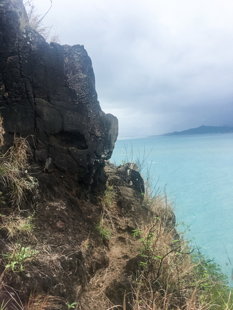 Chinamans Hat is the island of Mokolii off the coast of Oahu Hawaii. View from the extremely dangerous hike to the summit of the steep island. Stock Photo