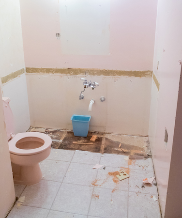 Bathroom with a pink toilette during demo day on a residential home renovation and major remodel.