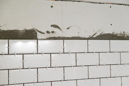 Tub surround voor een lange douche met witte ondergronds tegels verticaal op cement bakplaat tijdens een grote woning renovatie.