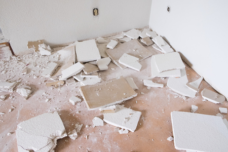 trashed: House renovation and major remodel with drywall making a huge mess as a wall is torn down at a construction site. Stock Photo