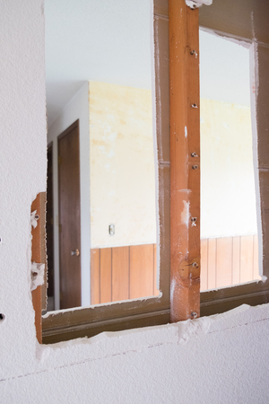 House renovation and major remodel with drywall making a huge mess as a wall is torn down at a construction site. Stock Photo