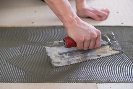 Tile setter laying down thinset for a tiling project during a major house renovation. Stock Photo
