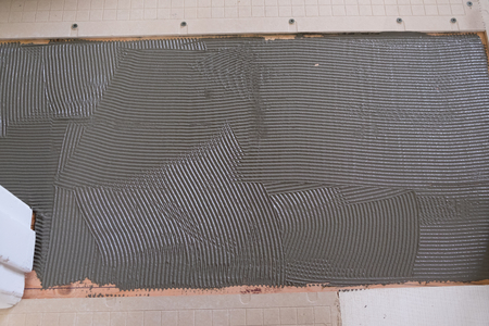 Tegel thinset modder (ook cement genoemd) voor een groots betegeld renovatieproject tijdens een woningrenovatie.