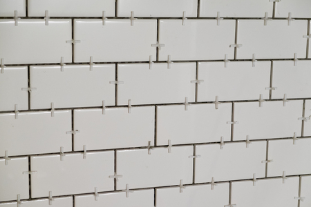 Tub surround for a tall shower with white subways tiles set vertically on cement backer board during a major home renovation.
