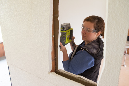 renovated: SPRINGFIELD, OR - DECEMBER 20, 2017: Female construction worker and homeowner using a sawsall tool to cut drywall out and take a wall down to a half-wall during a DIY house renovation.