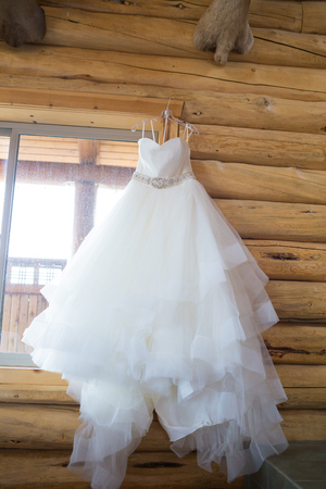 Bride Wedding Dress Hanging in Lodge Foto de archivo