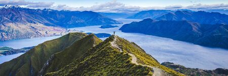 Roys peak mountain hike in Wanaka New Zealand. Popular tourism travel destination. Concept for hiking travel and adventure. New Zealand landscape background.