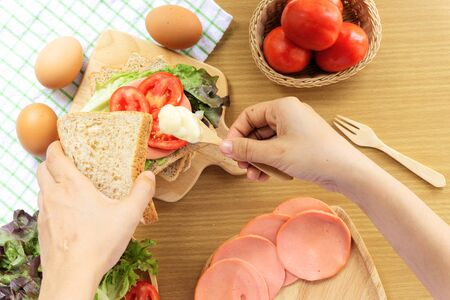 Homemade sandwich breakfast preparing. Whole wheat bread is stacked on a wooden cutting board placed on a white fabric, green checkered pattern. Slice tomatoes and lettuce placed on a wooden plate. Fresh tomatoes, ham, eggs, spoon and fork lay on a wooden table. Cooking ingredient. Food background concept with copyspace. 版權商用圖片
