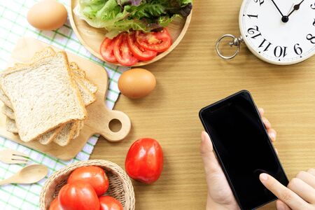 Homemade sandwich breakfast preparing. Whole wheat bread is stacked on a wooden cutting board placed on a white fabric, green checkered pattern. Smart phone, slice tomatoes and lettuce placed on a wooden plate. Fresh tomatoes, ham, eggs, spoon and fork lay on a wooden table. Cooking ingredient. Food background concept with copyspace.