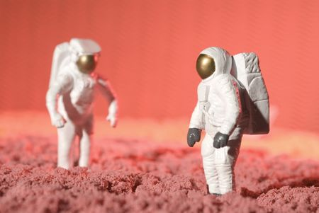 two astronauts figurines walking and discovering a planet
