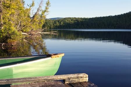 Dit is een groene kano hechten aan een dek onver een rustig meer bij zonsondergang.