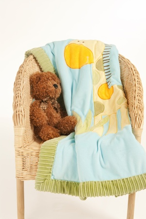 This is a brown teddy bear seating on a rattan chair isolated over a white background. photo