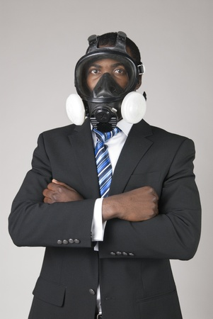 This is a black businessman waring a gas mask isolated over a gray background. photo