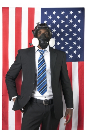 This is a black businessman waring a gas mask isolated over a American flag.