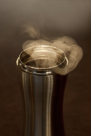 This is a hot coffee with smoke in a stainless steal mug on a kitchen counter. Фото со стока
