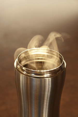 This is a hot coffee with smoke in a stainless steal mug on a kitchen counter. photo