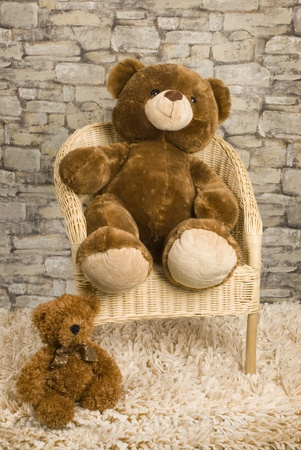 This is a rotin chair with bears on it over a stone wall and a teddy bear biside.