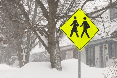 This is a yellow sign of students crossing with a peed limit in a snow storm. Stock fotó