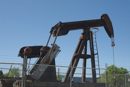 This is a pump jack surounded by barbed wire. Stock Photo - 11574200