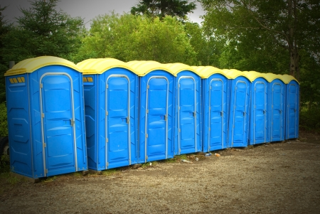 This is a row of yellow and blue portable toilet outside in the forest. Stock fotó