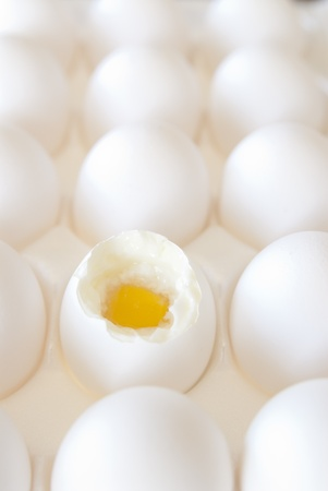 This is a bunch of white eggs in a white crete and one is open and half cooked. Stock Photo - 12156753