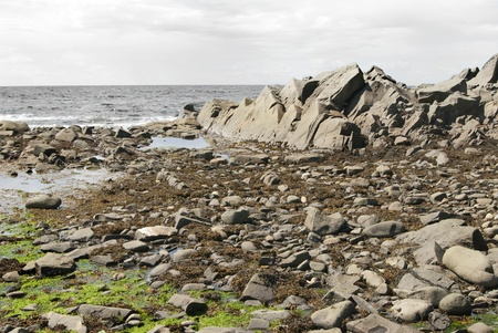 This is a bunch of big rocks close to the sea over a blue cloudy sky. photo