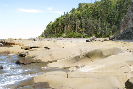 This is a  bunch of stones on a beach of the St-Lauwrence river et therre is a cliff beside. photo