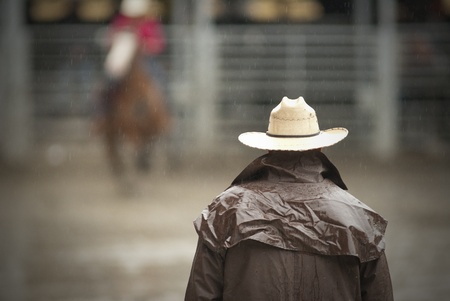 A male cowboy waiting standing up under the rain in a statdium and we see him from the back. Stock fotó