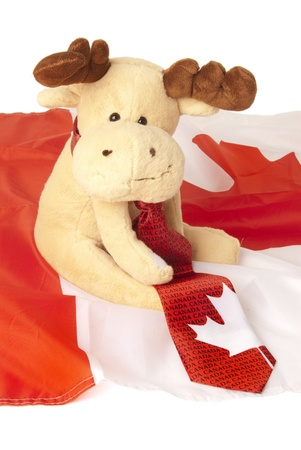 This is a moose toy seating over a canadian flag and wearing a canadian tie. photo