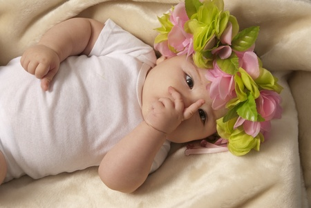 This is a little baby girl laying down over a beige blanket and wearing a flower crown  photo