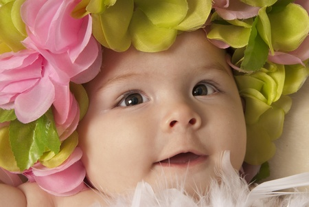 This is a close-up of a little baby girl laying down over a beige blanket and wearing a flower crown  photo