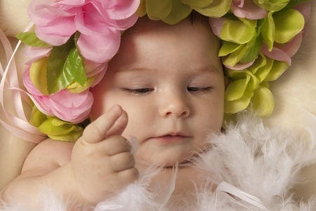 This is a close-up of a little baby girl laying down over a beige blanket and wearing a flower crown and playing with white feathers