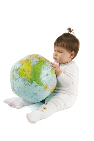 This is a little baby girl playing with an inflatable globe isolated over a white background