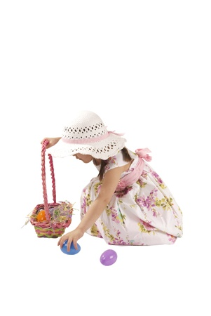This is a little girl looking for eggs at Easter with a white dress and isolated on a white background. Stock Photo - 12461450