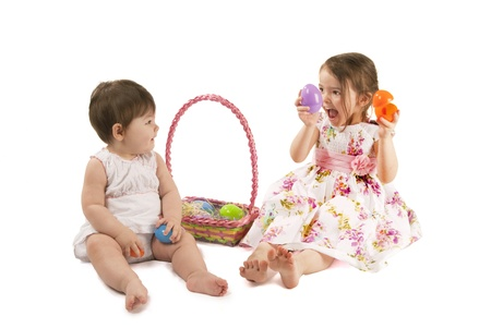 This is two little girl with a dress playing with eggs for Easter isolated on a white background.