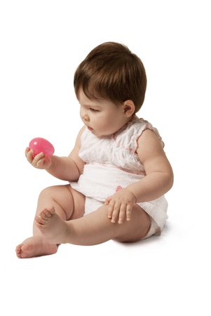 This is a little baby girl playing Easter eggs hunt isolated over a white background. Stock fotó