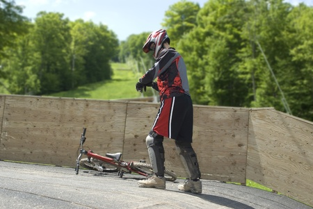This is a guy fixing is equipment to ride a mountain bike. photo