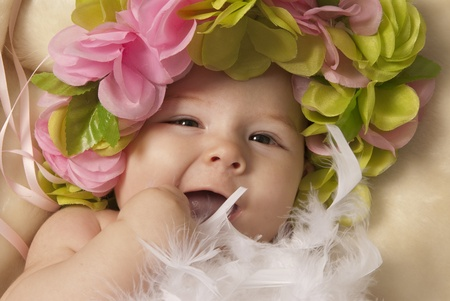 A close-up of a little baby girl laying down over a beige blanket and wearing a flower crown and playing with white feathers  Stock fotó