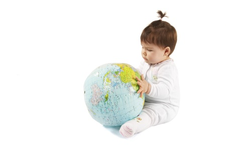 Little baby girl holding a inflatable planet earth over a white background