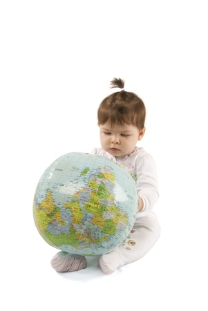 Little baby girl playing with an inflatable globe isolated over a white background Stock Photo - 12814346