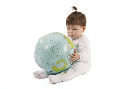 human evolution: Little baby girl playing with an inflatable globe isolated over a white background  Stock Photo