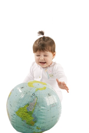 Little baby girl playing with an inflatable globe isolated over a white background.