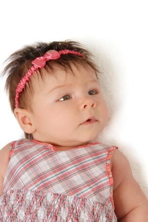 A close-up of a baby girl laying down on a white background. Stock fotó